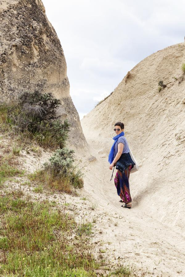 Turista della donna nella valle di Cappadocia Passeggiata nelle montagne sabbiose fotografia stock libera da diritti