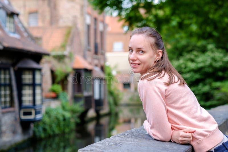 Turista della donna vicino al canale dell'acqua di Bruges, Fiandre, Belgio fotografie stock