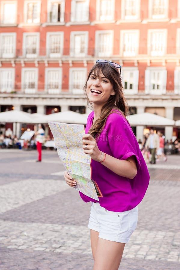Turista della giovane donna che tiene una mappa di carta fotografia stock