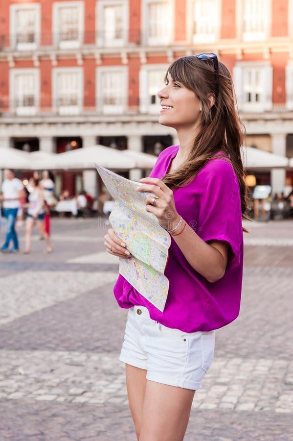 Turista della giovane donna che tiene una mappa di carta fotografie stock