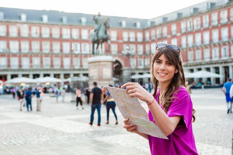 Turista della giovane donna che tiene una mappa di carta fotografia stock libera da diritti