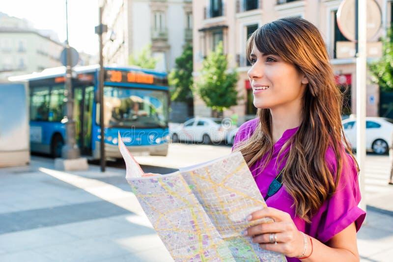 Turista della giovane donna che tiene una mappa di carta immagine stock