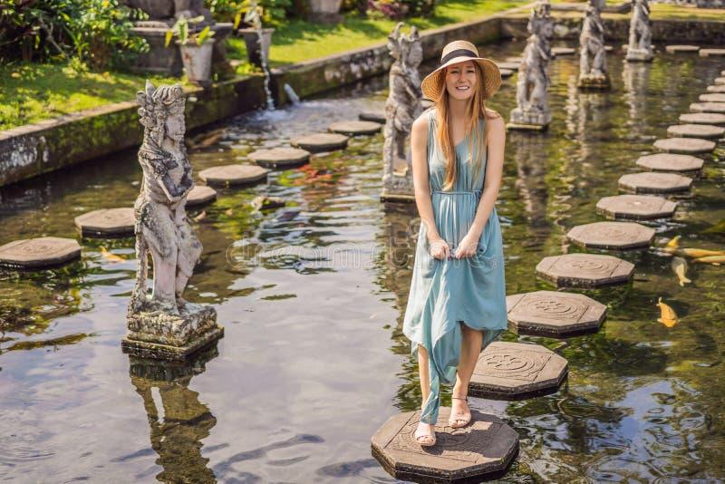 Turista della giovane donna in Taman Tirtagangga, palazzo dell'acqua, parco dell'acqua, Bali Indonesia fotografia stock