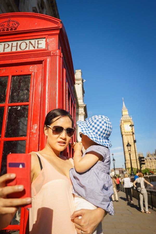 Turista della madre e del bambino di viaggio di Londra da Big Ben e dalla cabina telefonica rossa fotografia stock