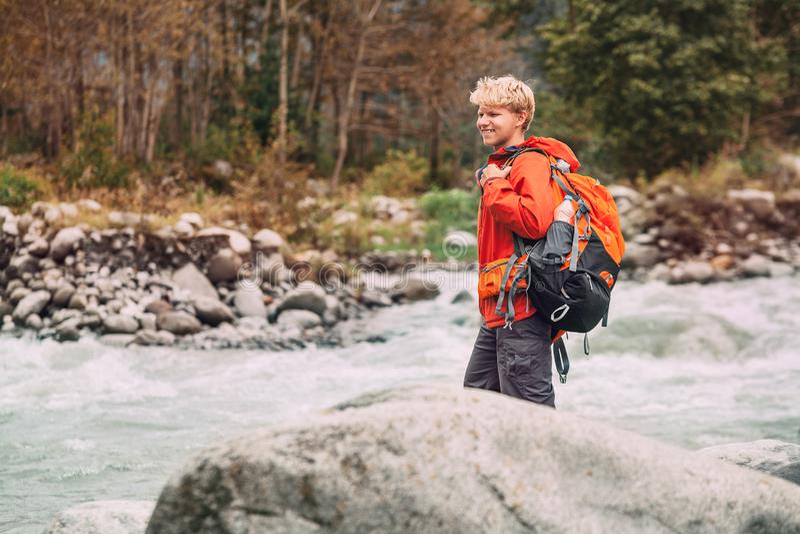 Turista do homem novo na floresta da montanha no banco de rio foto de stock
