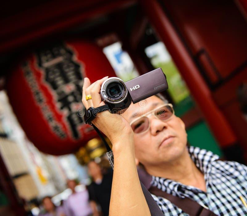 Turista dos sêniores que guarda uma câmara de vídeo imagens de stock