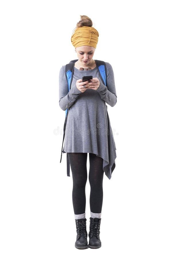 Turista elegante lindo joven de la mujer con la mochila que busca para los lugares en el app del teléfono móvil imagen de archivo libre de regalías
