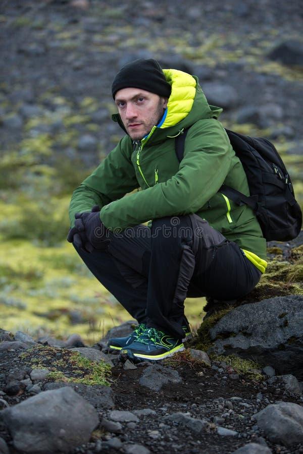 Turista em um revestimento verde que senta-se em uma pedra contra uma inclina??o rochosa coberto de vegeta??o com o musgo imagens de stock