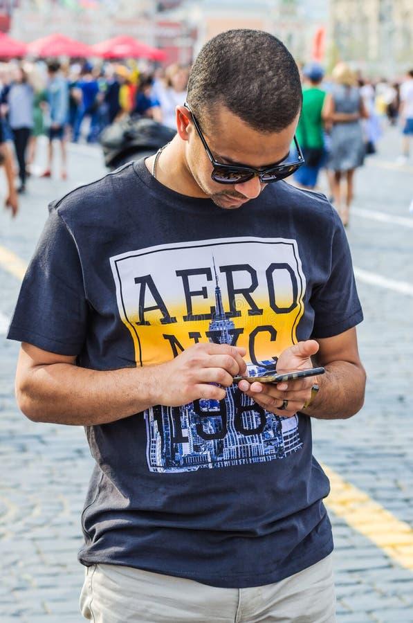 Turista em um t-shirt NYC AERO 1987 com um smartphone em suas mãos que anda no quadrado vermelho imagem de stock royalty free