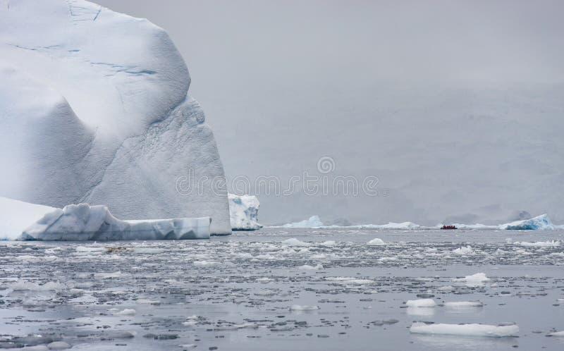 Turista em um zodíaco que viaja em águas antárticas imagens de stock