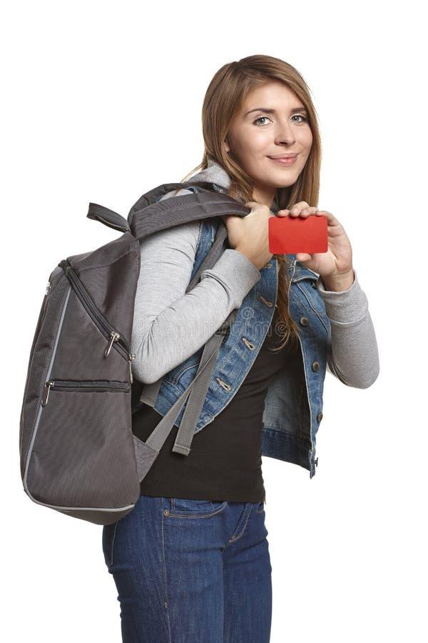Muchacha feliz con la mochila que muestra la tarjeta del crédito en blanco imagen de archivo