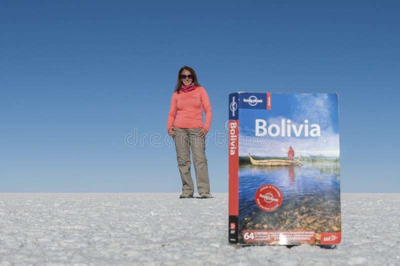 Turista en el plano de la sal de Uyuni que juega con la perspectiva espacial, creando una ilusión visual, Bolivia imagen de archivo libre de regalías
