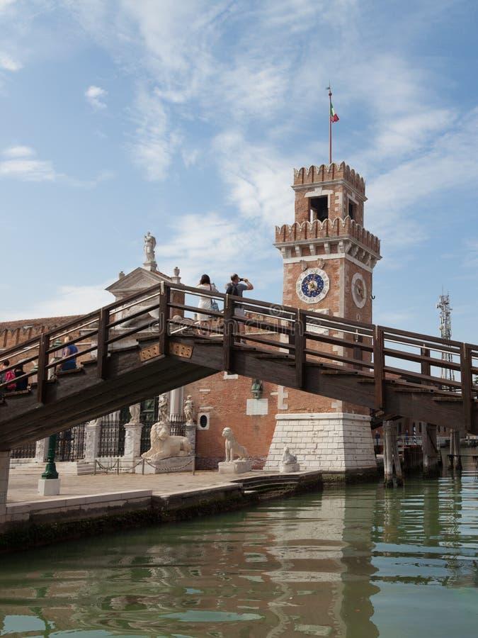 Turista en el puente que toma la foto con su teléfono elegante en la entrada del arsenal en Venecia imagen de archivo libre de regalías