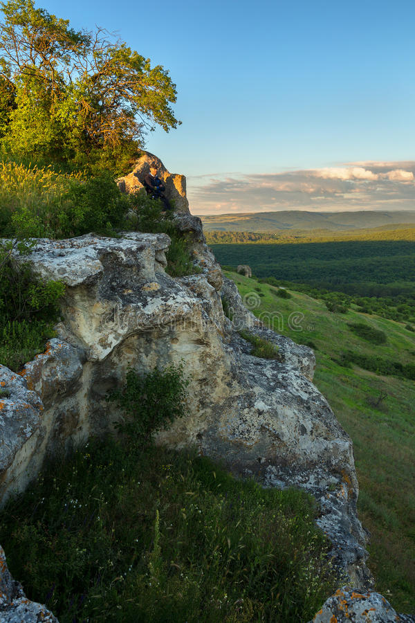 Turista en el trono de piedra en el top de la ciudad Bakla de la cueva en Bakhchysarai Raion fotos de archivo libres de regalías