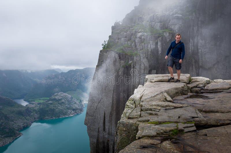 Turista en la roca de Prekestolen fotos de archivo