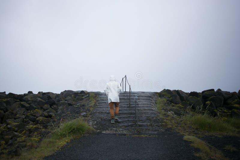 Turista en los paseos blancos del impermeable en la orilla de Islandia imagen de archivo libre de regalías
