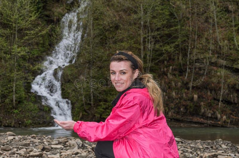 Turista encantador novo da menina no fundo de uma cachoeira da montanha imagens de stock royalty free