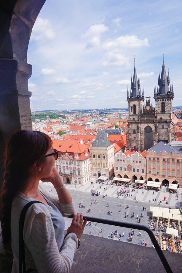 Turista fêmea asiático que olha abaixo da praça da cidade velha do obervatório da torre de pulso de disparo astronômica em Praga foto de stock
