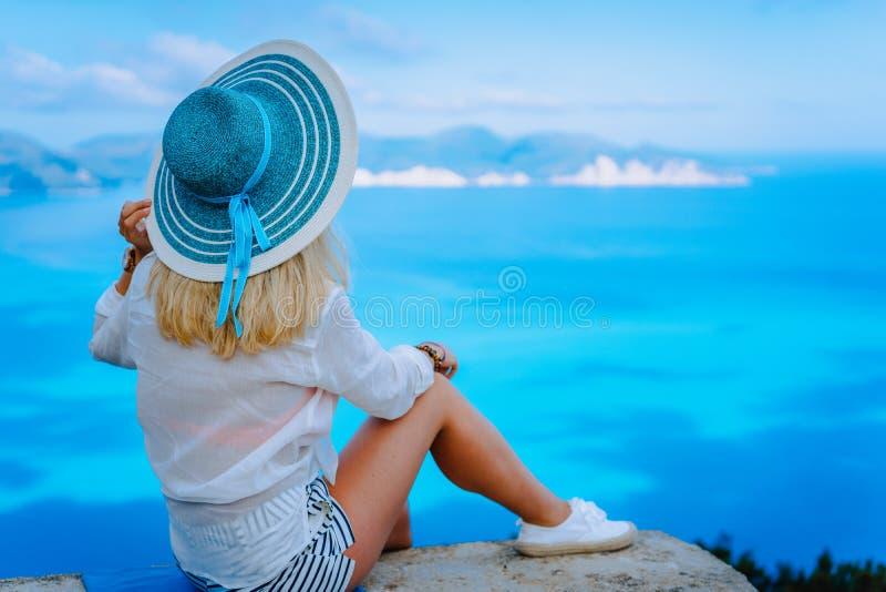 Turista fêmea atrativo com o chapéu do sol de turquesa que aprecia seascape surpreendente dos azuis celestes, Grécia Sombras de C imagens de stock royalty free