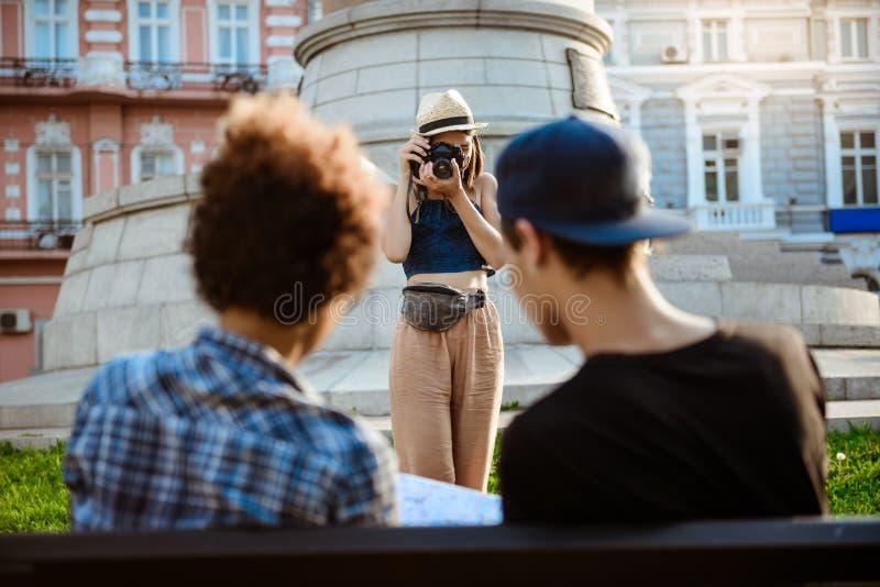 Turista fêmea bonito novo que toma a imagem de seus amigos imagens de stock royalty free