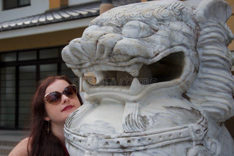 Turista fêmea caucasiano que levanta com a estátua de mármore branca do leão do dragão em Japão fotos de stock