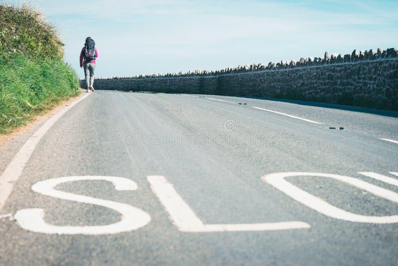 Turista fêmea, hichhiker, mochileiro andando na estrada a um d fotografia de stock royalty free