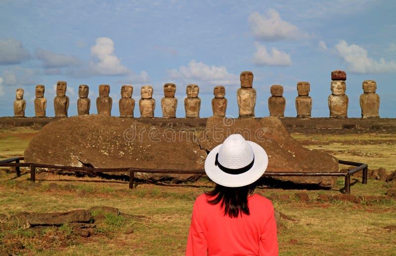 Turista fêmea impresso pelas ruínas de estátuas de Moai em Ahu Tongariki no local arqueológico da Ilha de Páscoa, o Chile imagens de stock royalty free