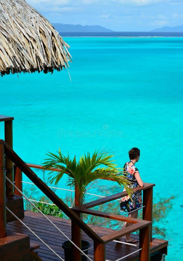 Turista fêmea no balcão de um bungalow do overwater fotos de stock royalty free