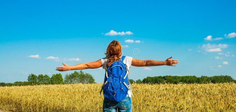 Turista fêmea novo com a trouxa que olha na distância perto de um campo de trigo sob o céu quente do verão fotos de stock