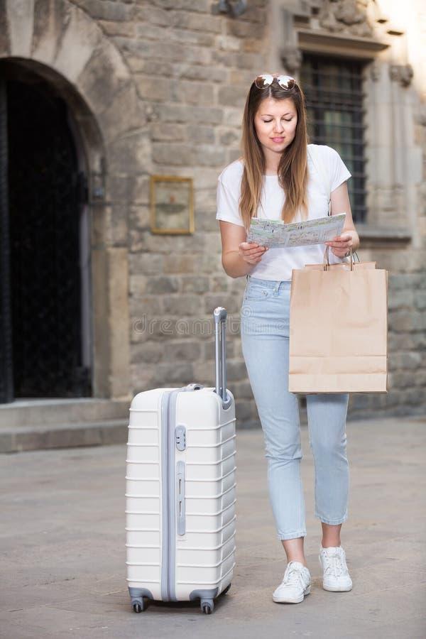 Turista fêmea novo louro que guarda o mapa nas mãos imagem de stock
