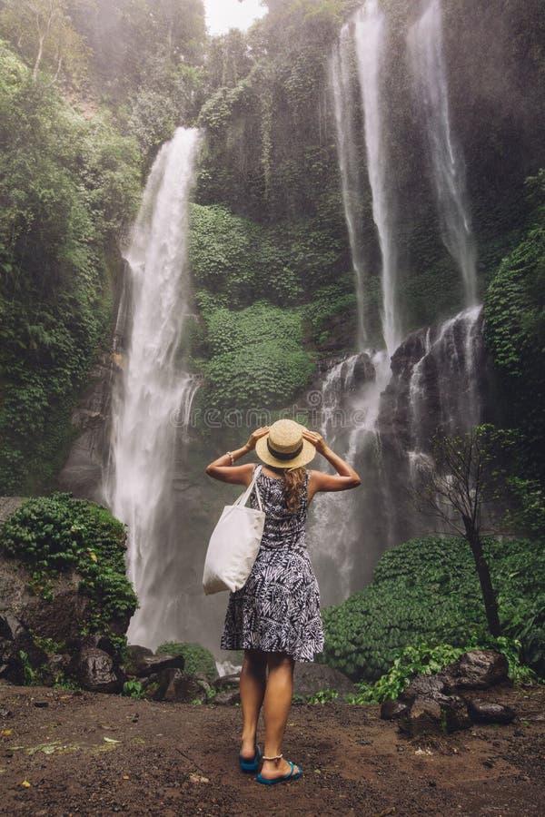 Turista fêmea que admira a cachoeira na floresta tropical imagens de stock