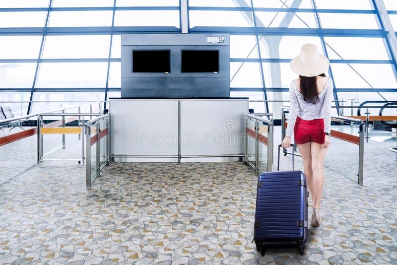 Turista fêmea que anda no terminal de aeroporto imagem de stock