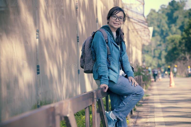 Turista fêmea que senta-se em um fence0 de madeira imagens de stock royalty free