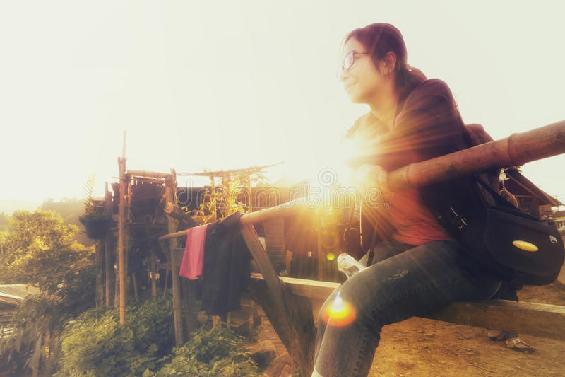 Turista fêmea que senta-se em uma luz solar de madeira da cadeira e da manhã imagem de stock royalty free