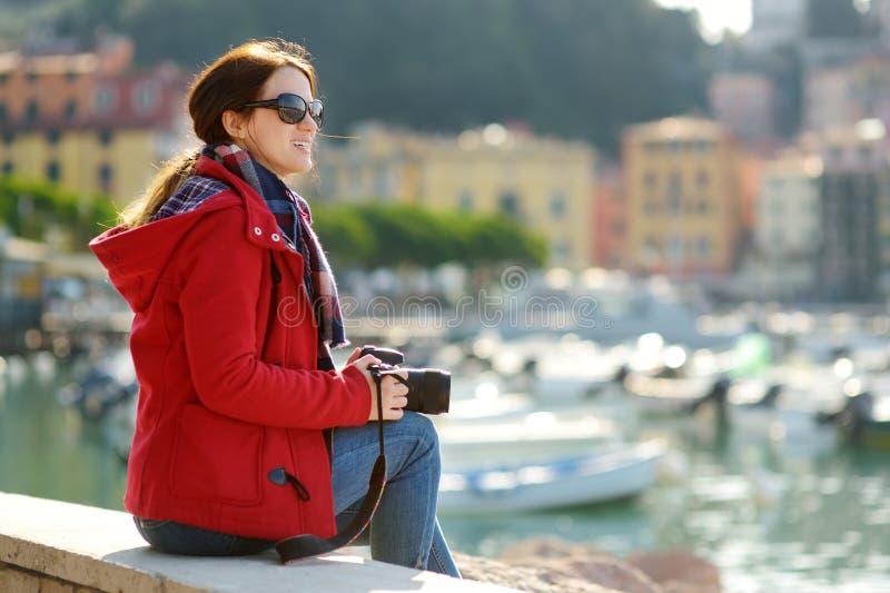 Turista f?mea novo que aprecia a vista de iate e de barcos de pesca pequenos no porto da cidade de Lerici, situado na prov?ncia d foto de stock royalty free