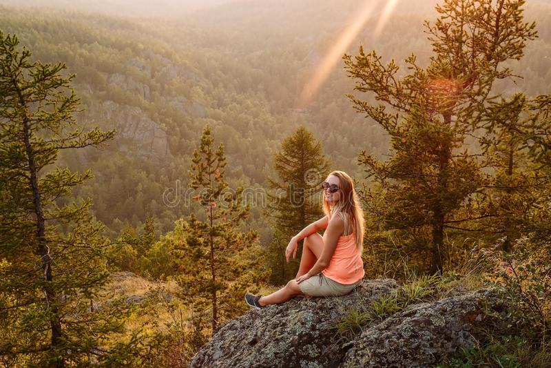 Turista felice biondo della donna in una maglietta arancio che si siede sull'orlo della montagna di estate al tramonto Paesaggio  immagini stock