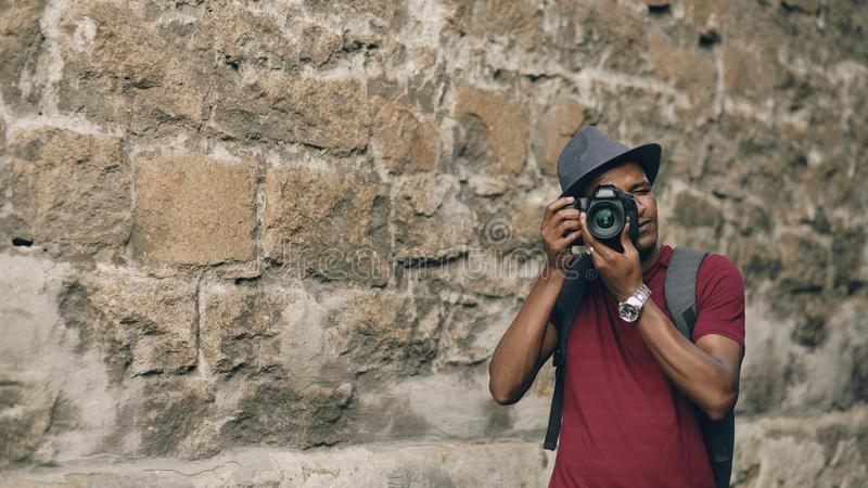 Turista feliz afro-americano que toma a foto em sua câmera do dslr Homem novo que está perto da construção famosa em Europa imagens de stock