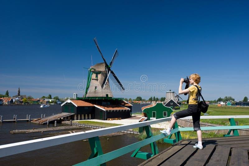 Turista feliz con la cámara de la foto y el molino holandés encendido fotos de archivo libres de regalías