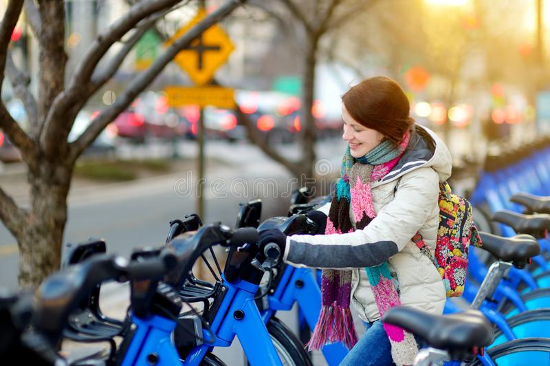 Turista feliz da jovem mulher pronto para montar uma bicicleta alugado em New York City no dia de mola ensolarado Viajante fêmea  fotos de stock royalty free