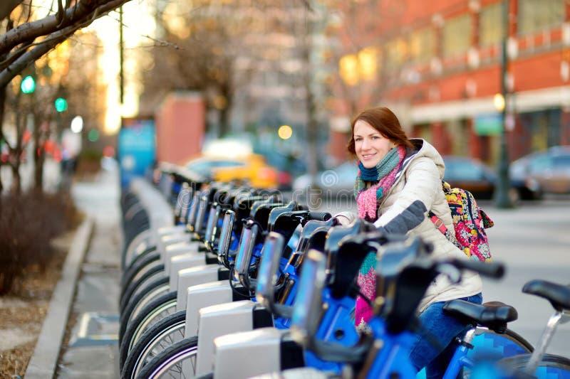 Turista feliz da jovem mulher pronto para montar uma bicicleta alugado em New York City no dia de mola ensolarado Viajante fêmea  foto de stock