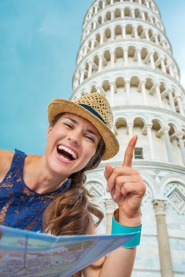 Turista feliz da mulher que guarda o mapa e que aponta na torre de Pisa imagens de stock