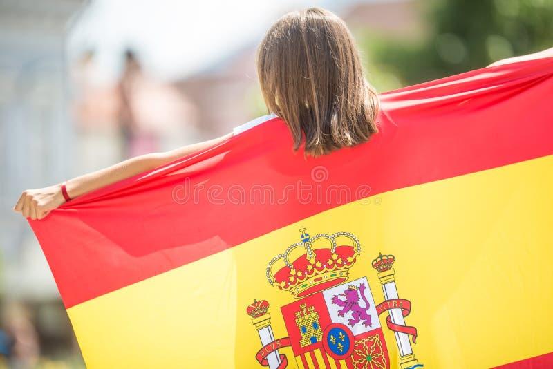 Turista feliz de la muchacha que camina en la calle con la bandera española foto de archivo