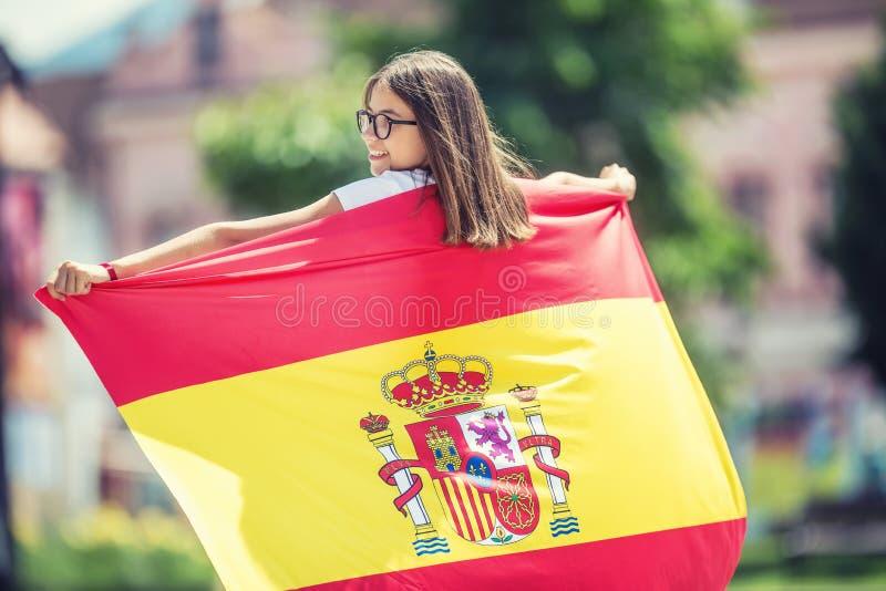 Turista feliz de la muchacha que camina en la calle con la bandera española fotos de archivo