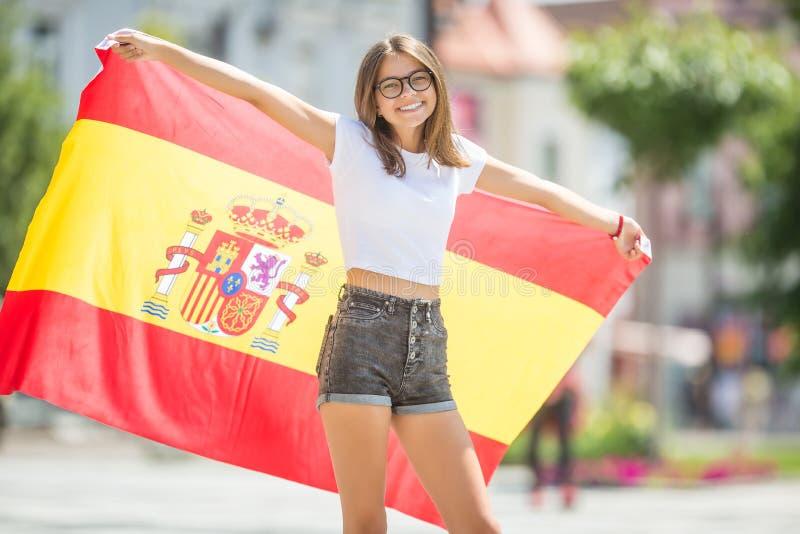 Turista feliz de la muchacha que camina en la calle con la bandera española fotografía de archivo