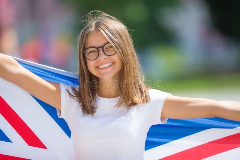 Turista feliz de la muchacha que camina en la calle con la bandera de Gran Bretaña foto de archivo