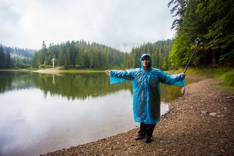 Turista feliz de las mujeres 60 años en el impermeable que disfruta de hermosa vista del lago grande de la montaña imagenes de archivo
