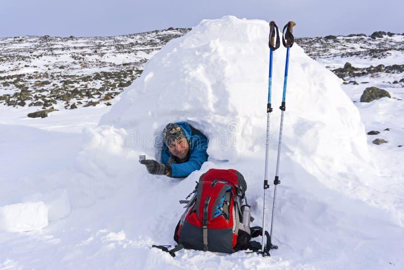Turista feliz de sorriso em um iglu nevado da casa com um vinho-vidro do metal da bebida do álcool imagens de stock