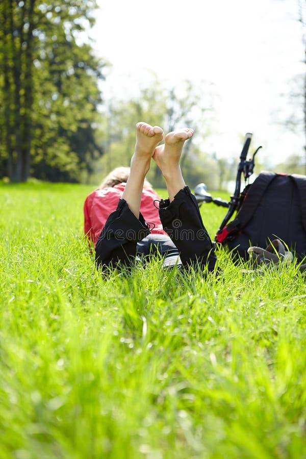 Turista feliz que aprecia o abrandamento que encontra-se com os pés descalços na grama verde imagens de stock royalty free