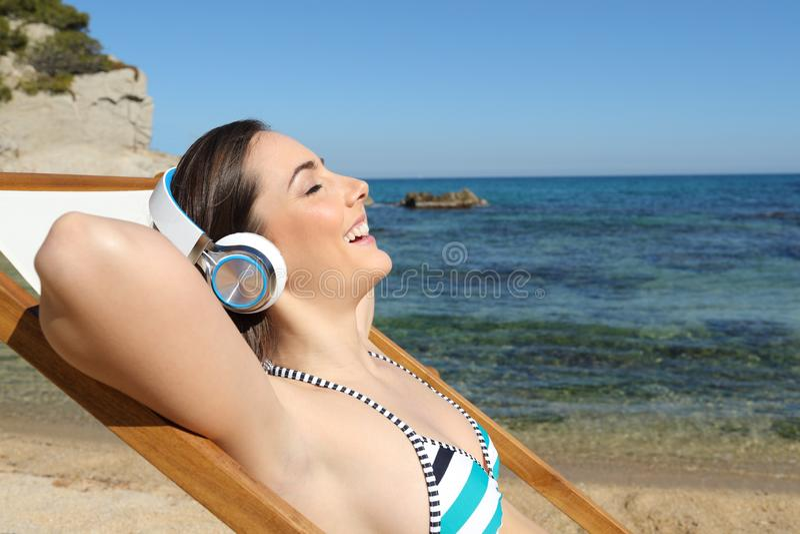 Turista feliz que escucha la música que se relaja en la playa foto de archivo libre de regalías