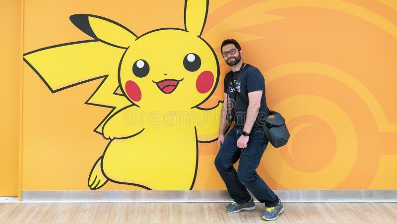 Turista feliz que levanta com uma figura de Pokemon Pikachu na loja do centro de Pokemon no shopping da cidade da luz do sol imagem de stock